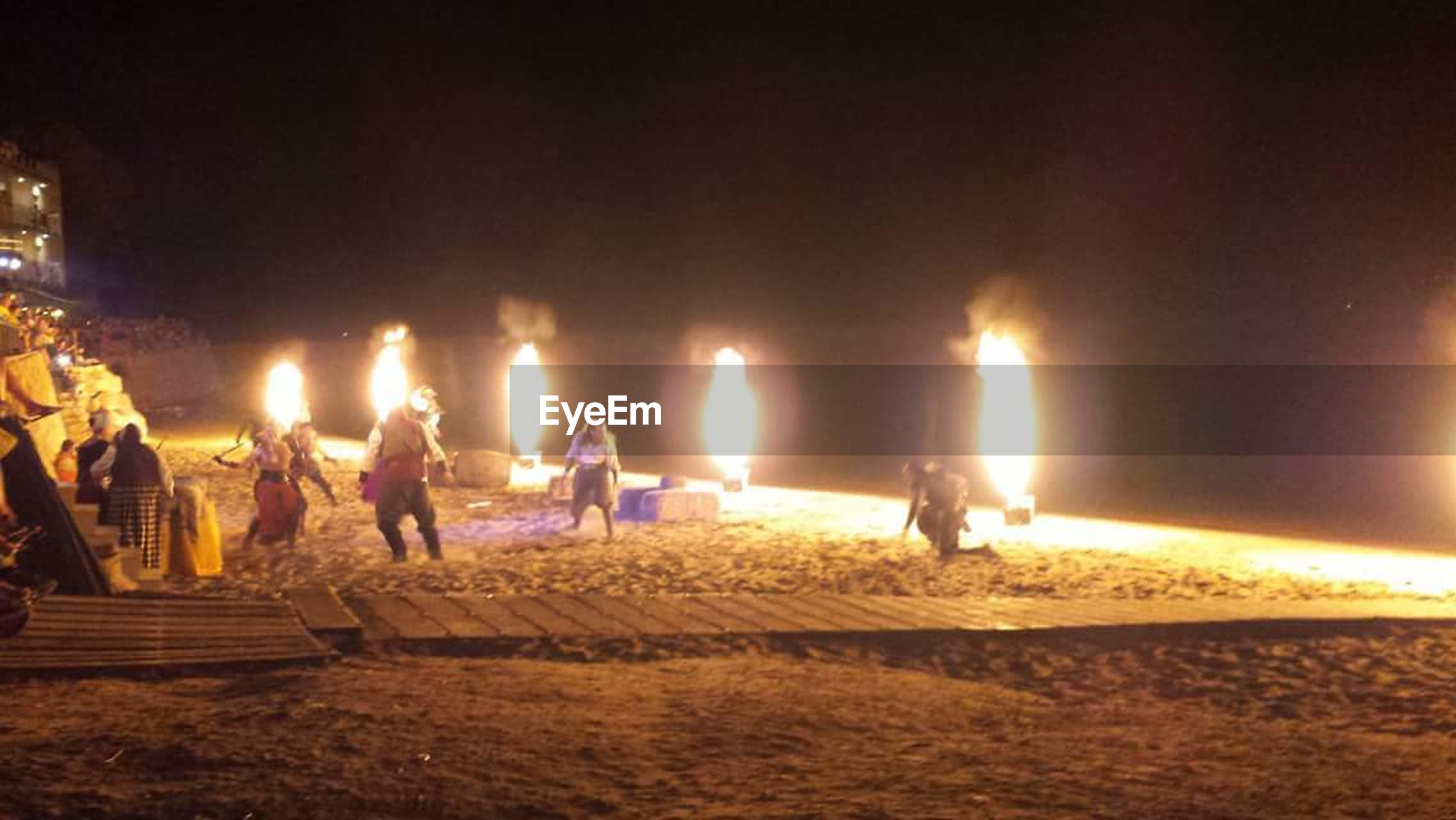 flame, night, beach, lifestyles, heat - temperature, togetherness, men, illuminated, outdoors, burning, sand, adult, people, ceremony, large group of people, only men, adults only