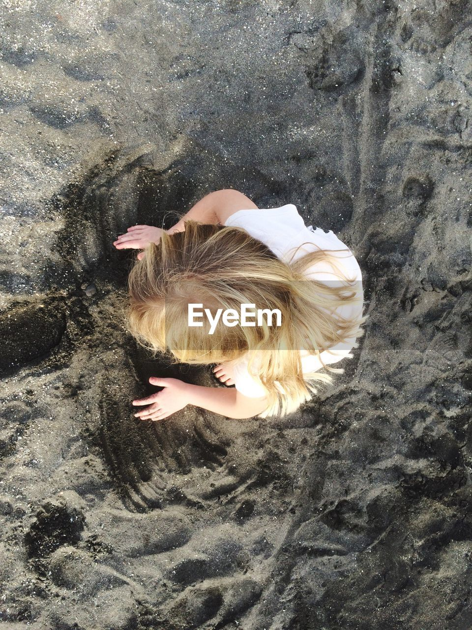 Directly above view of girl playing with sand at beach
