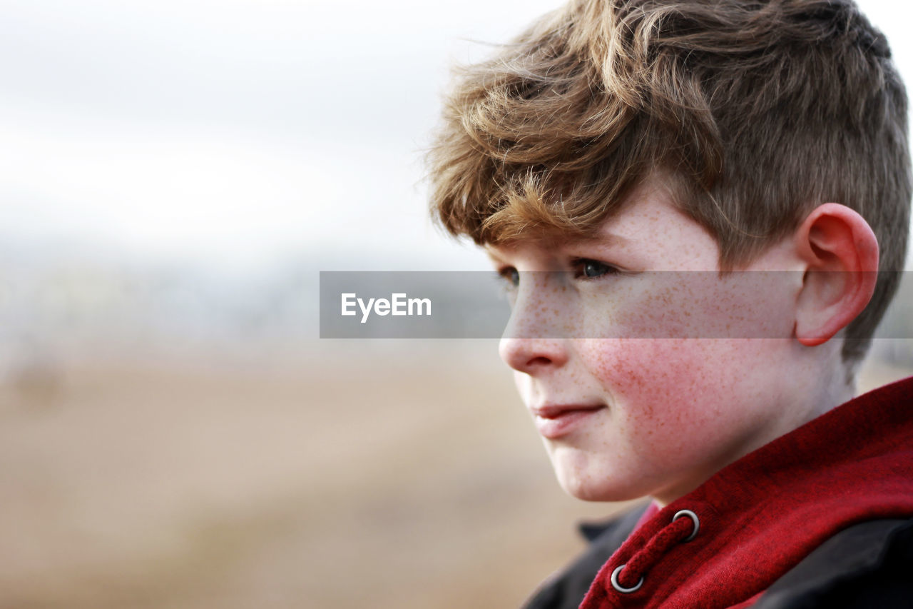 portrait, headshot, one person, focus on foreground, looking, looking away, side view, day, young adult, real people, close-up, lifestyles, boys, child, contemplation, young men, outdoors, brown hair, teenage boys, adolescence, teenager, hairstyle, human face, profile view