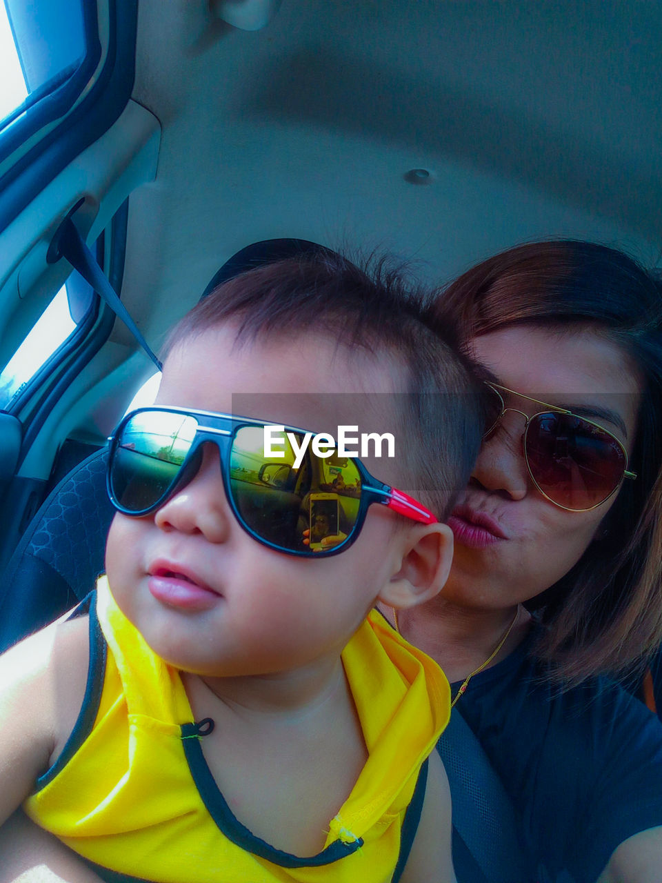 portrait, sunglasses, headshot, females, childhood, front view, lifestyles, glasses, vehicle interior, real people, two people, women, bonding, leisure activity, mode of transportation, child, togetherness, fashion, transportation, innocence