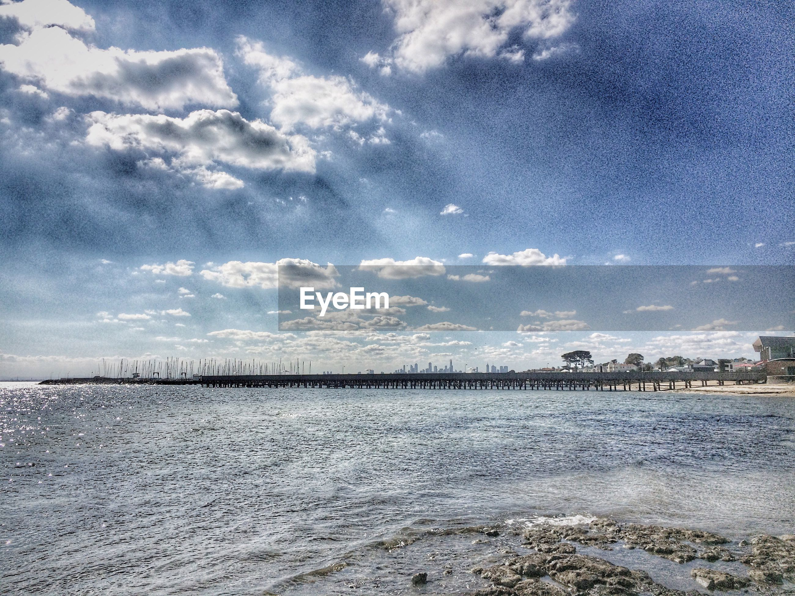 water, sky, sea, cloud - sky, scenics, beach, tranquil scene, tranquility, cloudy, beauty in nature, cloud, nature, shore, waterfront, built structure, architecture, coastline, outdoors, idyllic, horizon over water