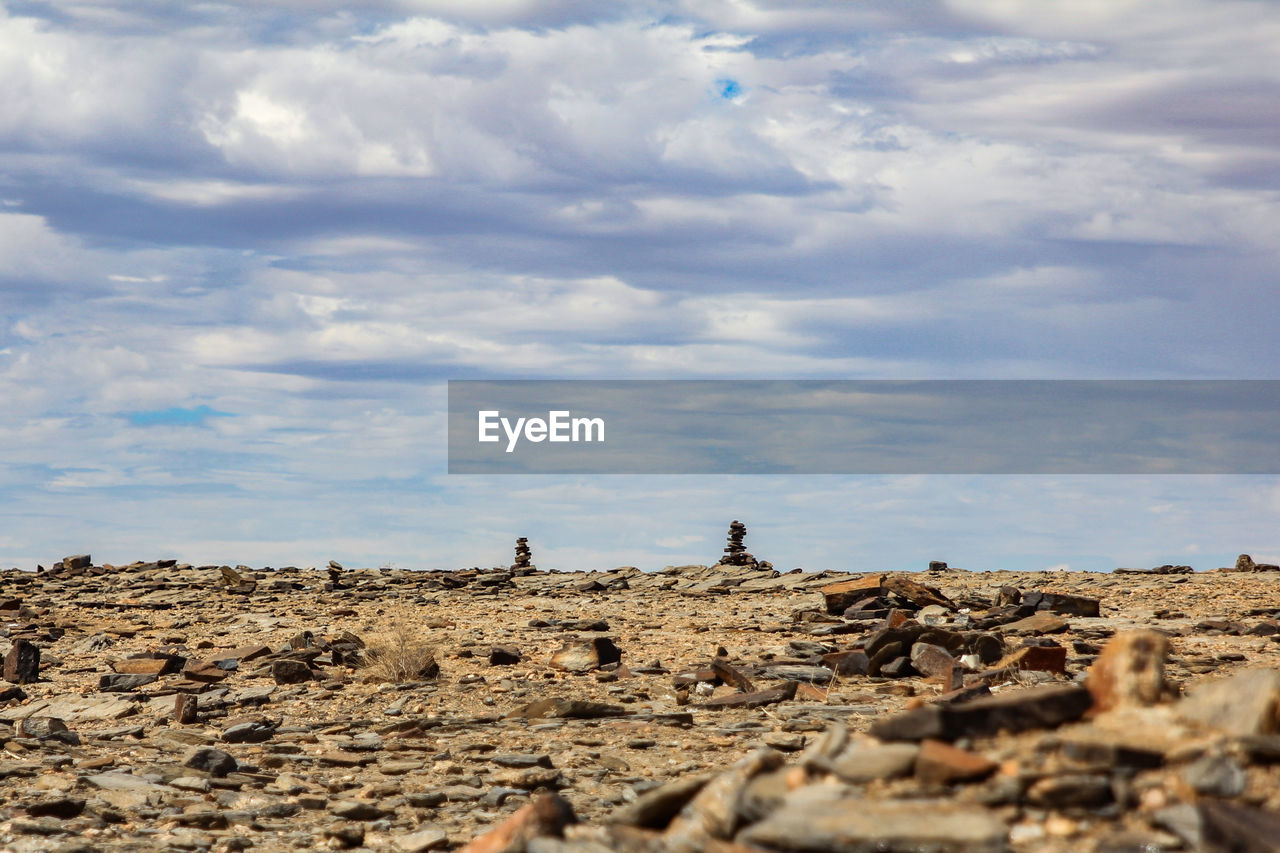 cloud - sky, sky, nature, land, day, environment, scenics - nature, landscape, tranquility, beauty in nature, tranquil scene, solid, leisure activity, non-urban scene, outdoors, rock, people, men, real people, horizon, climate, arid climate, surface level