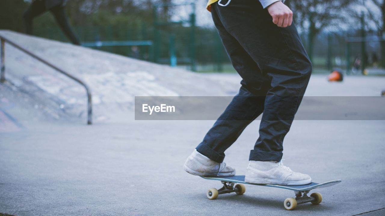 low section, skateboard, real people, human leg, one person, sport, leisure activity, balance, skateboard park, outdoors, lifestyles, day, road, standing, snow, cold temperature, skill, winter, human body part, ice skate, ice rink, people