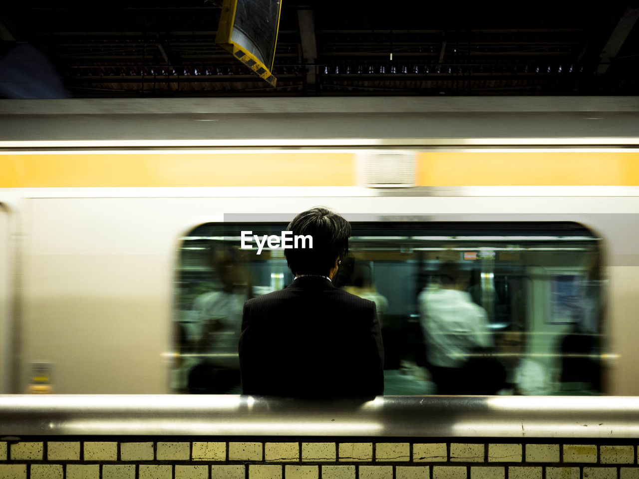 Passenger Looking At Blurred Motion Of Train In Subway