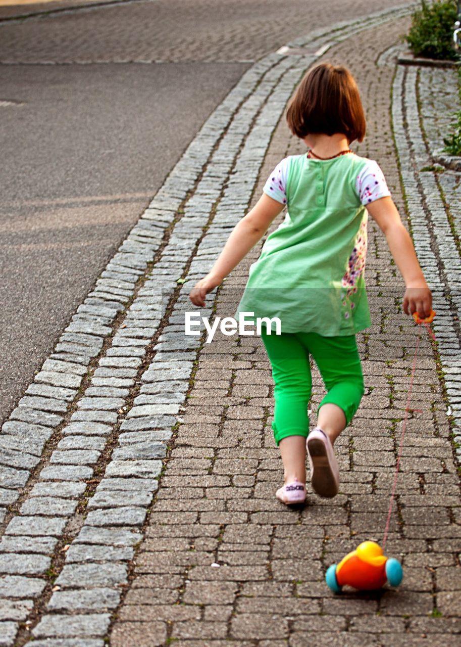 FULL LENGTH OF GIRL PLAYING ON COBBLESTONE