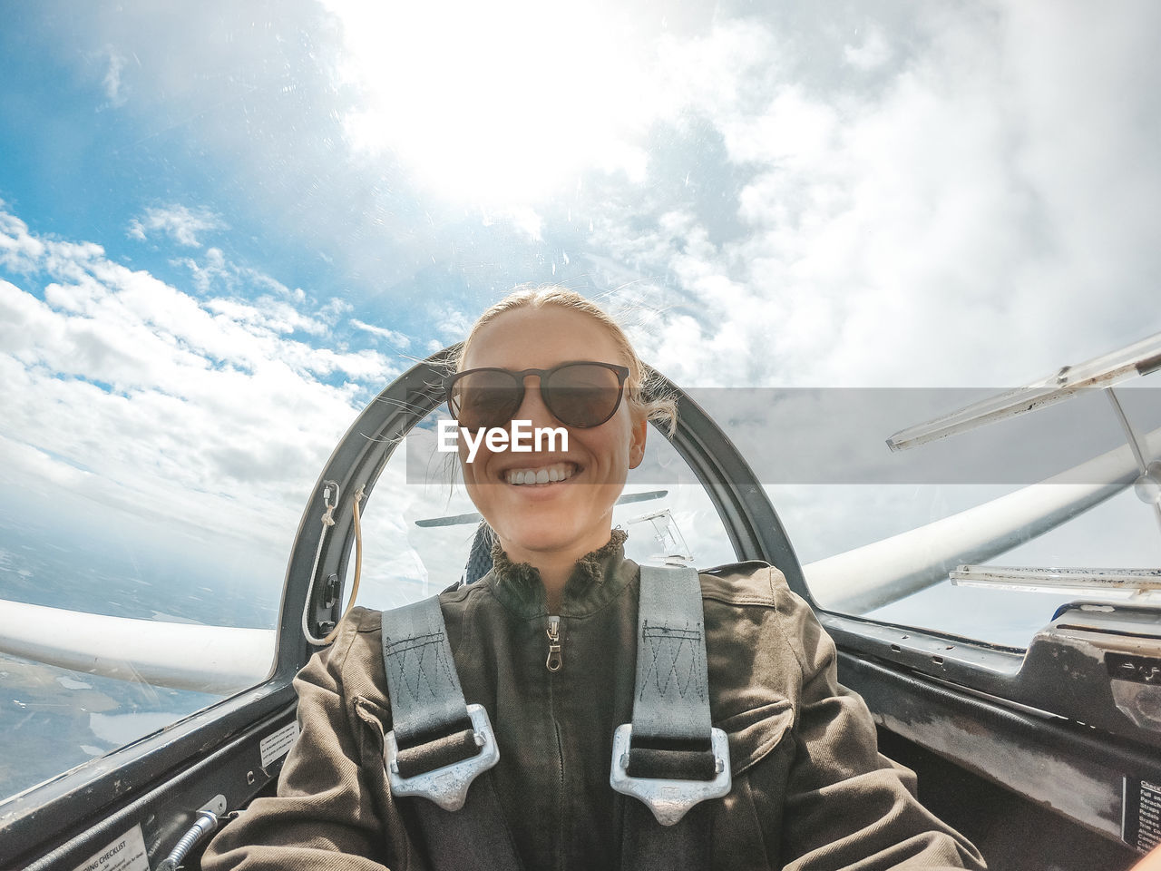 transportation, smiling, mode of transportation, glasses, portrait, one person, real people, front view, young adult, cloud - sky, day, sky, lifestyles, adult, travel, happiness, nature, young women, women, fashion, outdoors