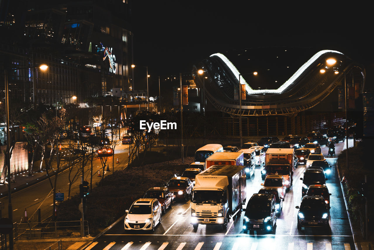 night, transportation, illuminated, mode of transportation, car, motor vehicle, city, land vehicle, street, architecture, road, building exterior, built structure, city life, traffic, travel, street light, high angle view, city street, motion, cityscape, nightlife
