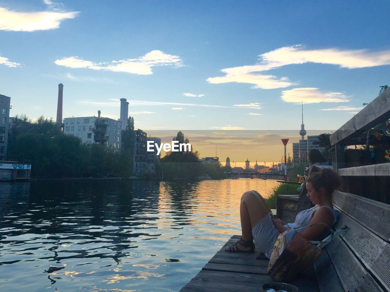 architecture, building exterior, built structure, water, sky, sitting, real people, city, cloud - sky, leisure activity, outdoors, two people, river, women, cityscape, togetherness, lifestyles, skyscraper, full length, sunset, day, urban skyline, nature, adult, people