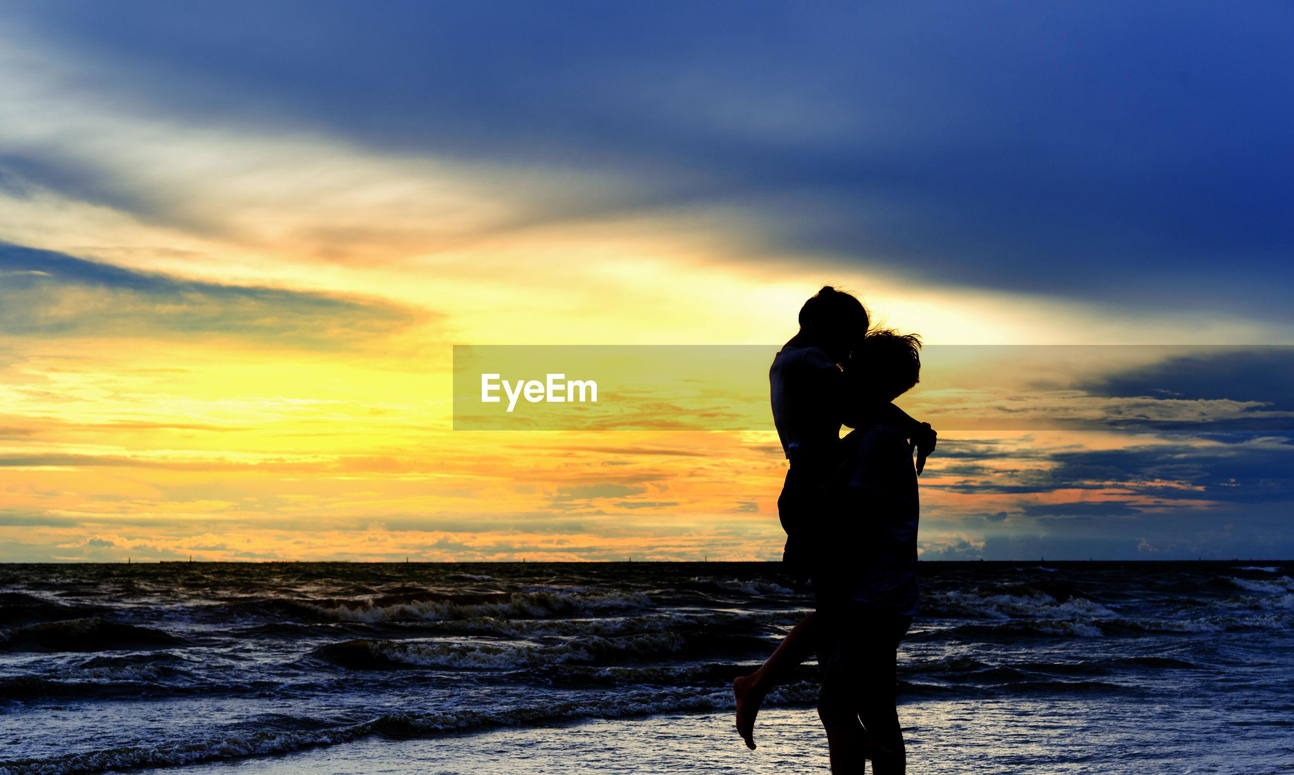 Man lifting girlfriend at beach during sunset