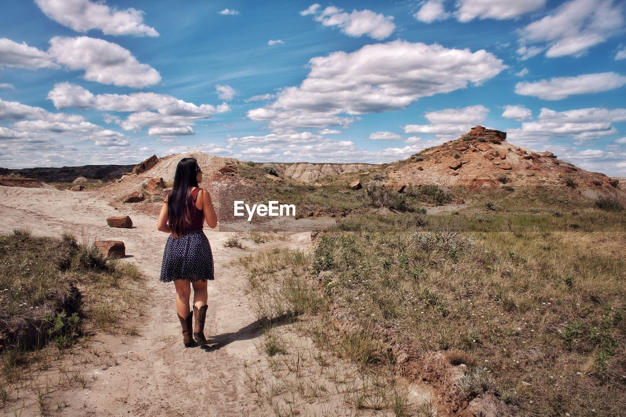 Rear view of woman standing in badlands against sky