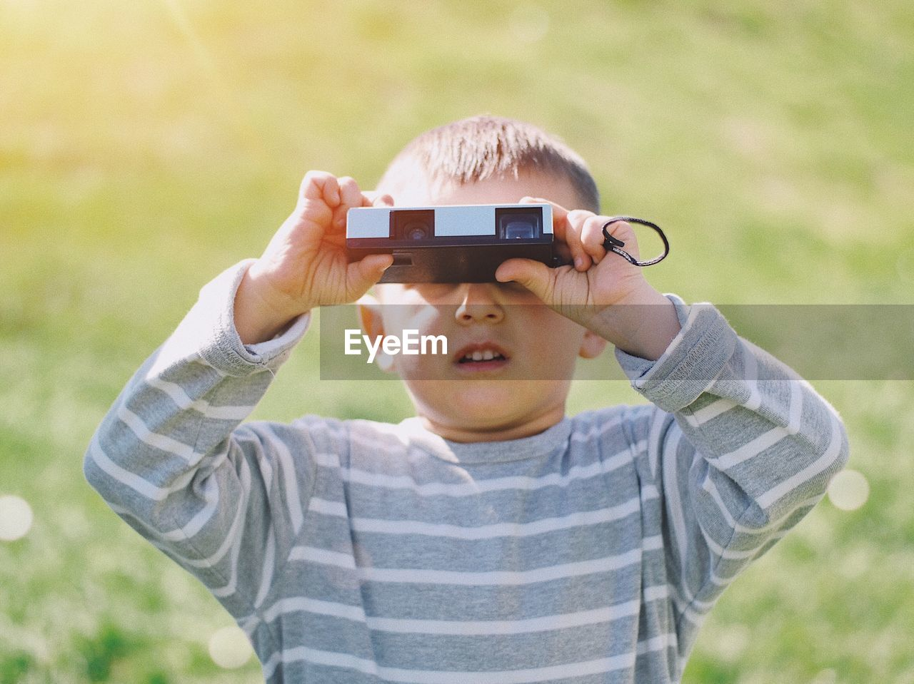 Boy looking through binoculars on grass