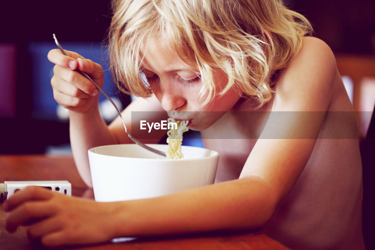 Shirtless Blond Boy Eating Noodles On Table At Home