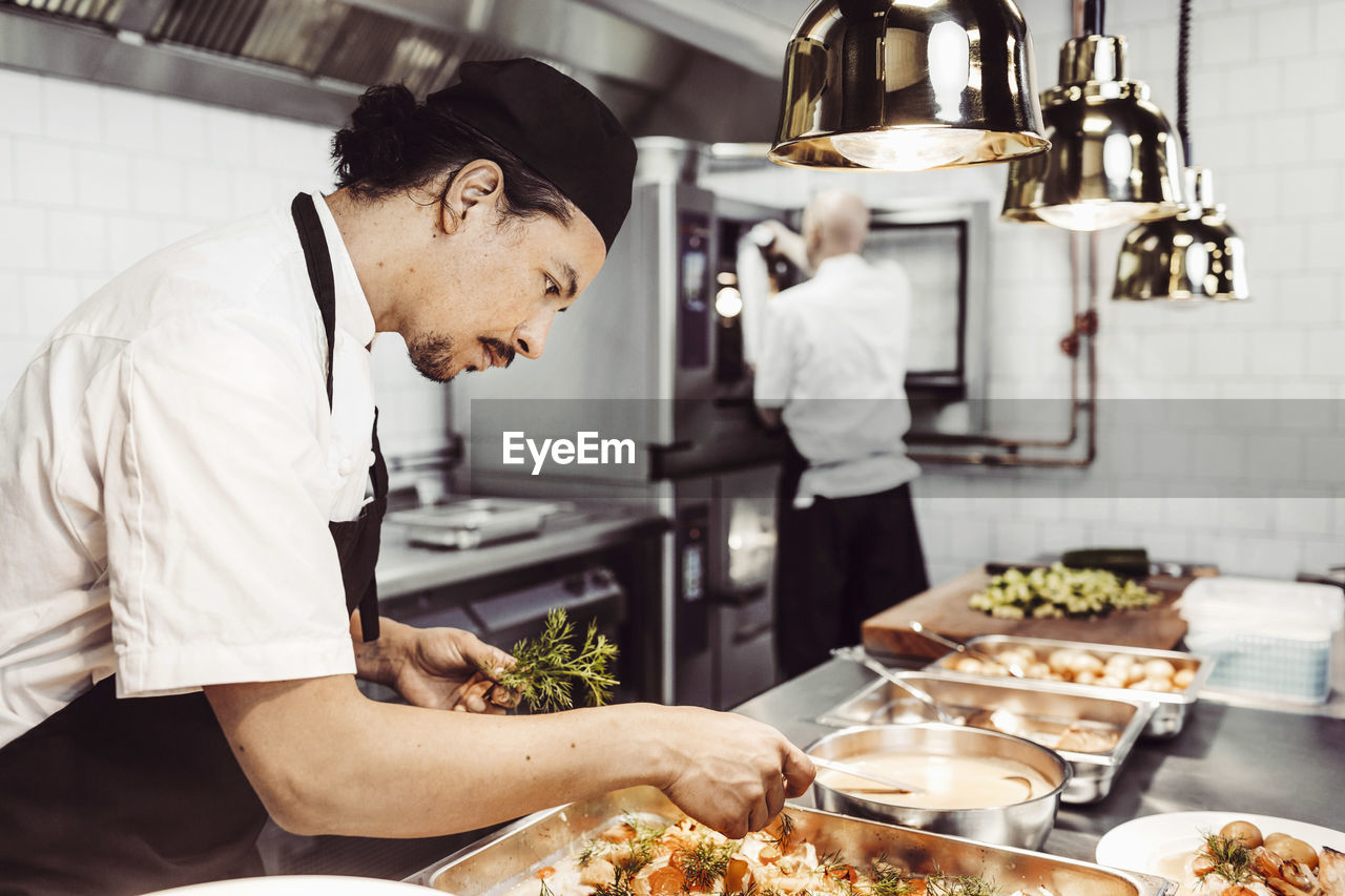 food and drink, kitchen, real people, commercial kitchen, occupation, indoors, food, preparation, one person, business, domestic room, food and drink establishment, standing, restaurant, freshness, kitchen counter, chef, working, men, preparing food, uniform