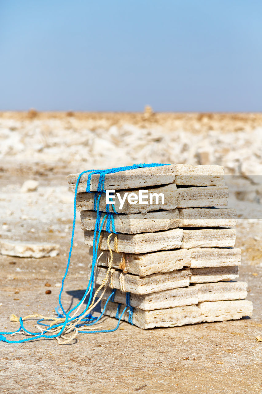 focus on foreground, day, sky, blue, stack, land, no people, nature, beach, sand, sunlight, damaged, wood - material, copy space, close-up, outdoors, still life, large group of objects, clear sky, obsolete