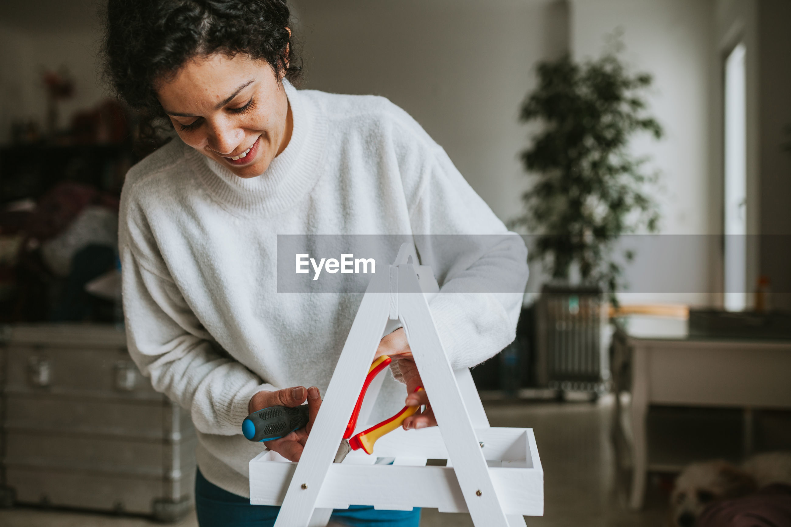 Woman repairing object at home