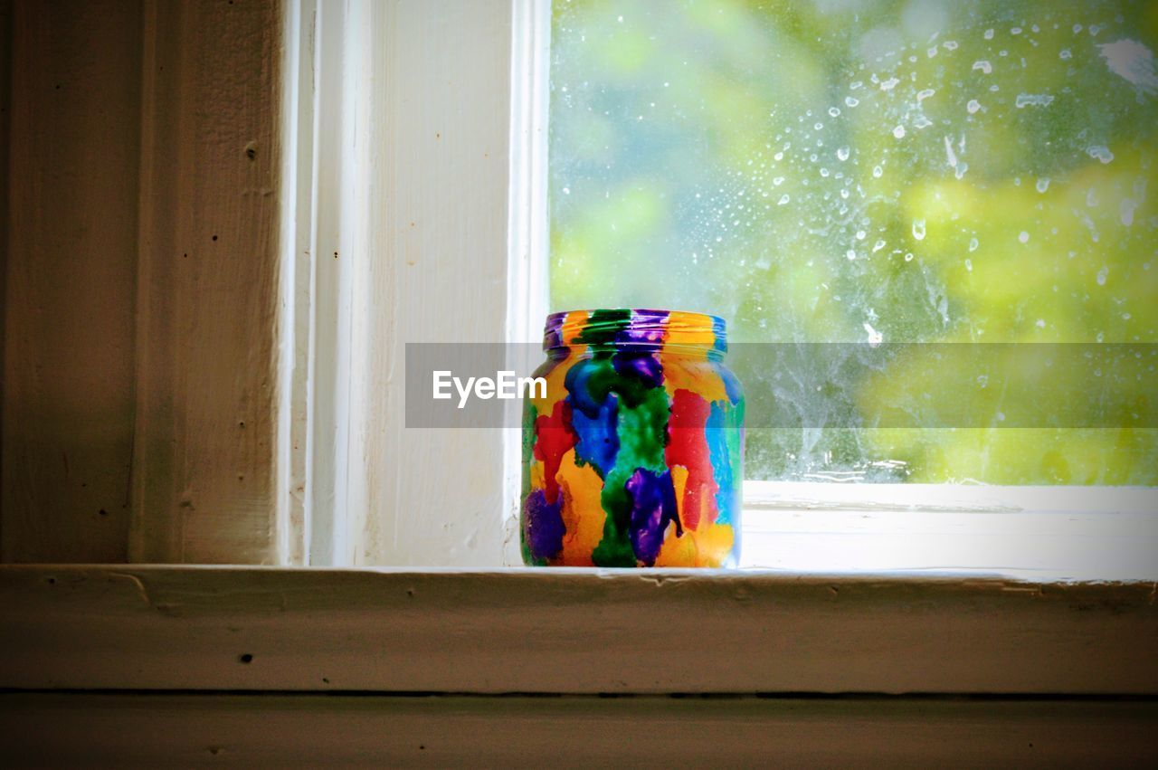 multi colored, indoors, glass - material, window, no people, still life, container, table, close-up, transparent, day, art and craft, glass, window sill, water, motion, wood - material, variation