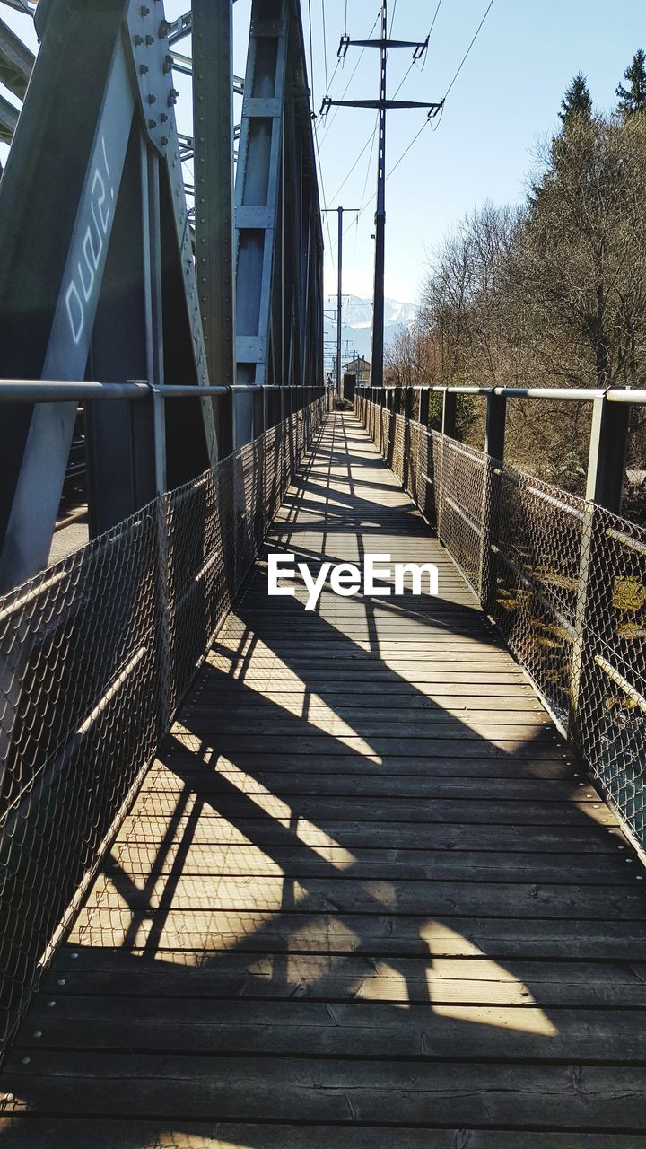 shadow, sunlight, nature, the way forward, architecture, direction, built structure, day, railing, sky, no people, bridge, tree, empty, bridge - man made structure, outdoors, connection, footpath, plant, footbridge, diminishing perspective, long