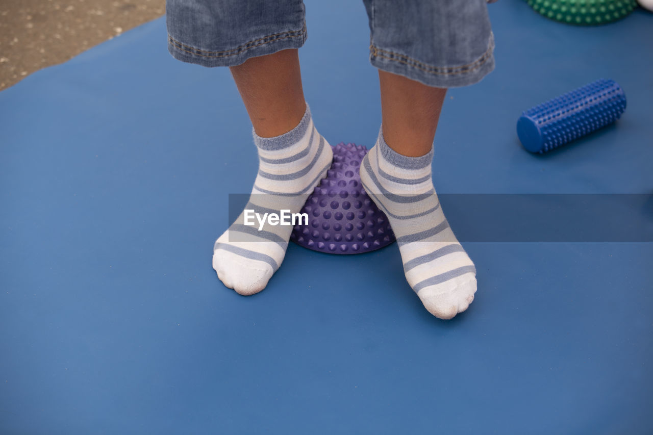 Low Section Of Boy Wearing Socks Standing On Spiked Balls While Exercising In Gym