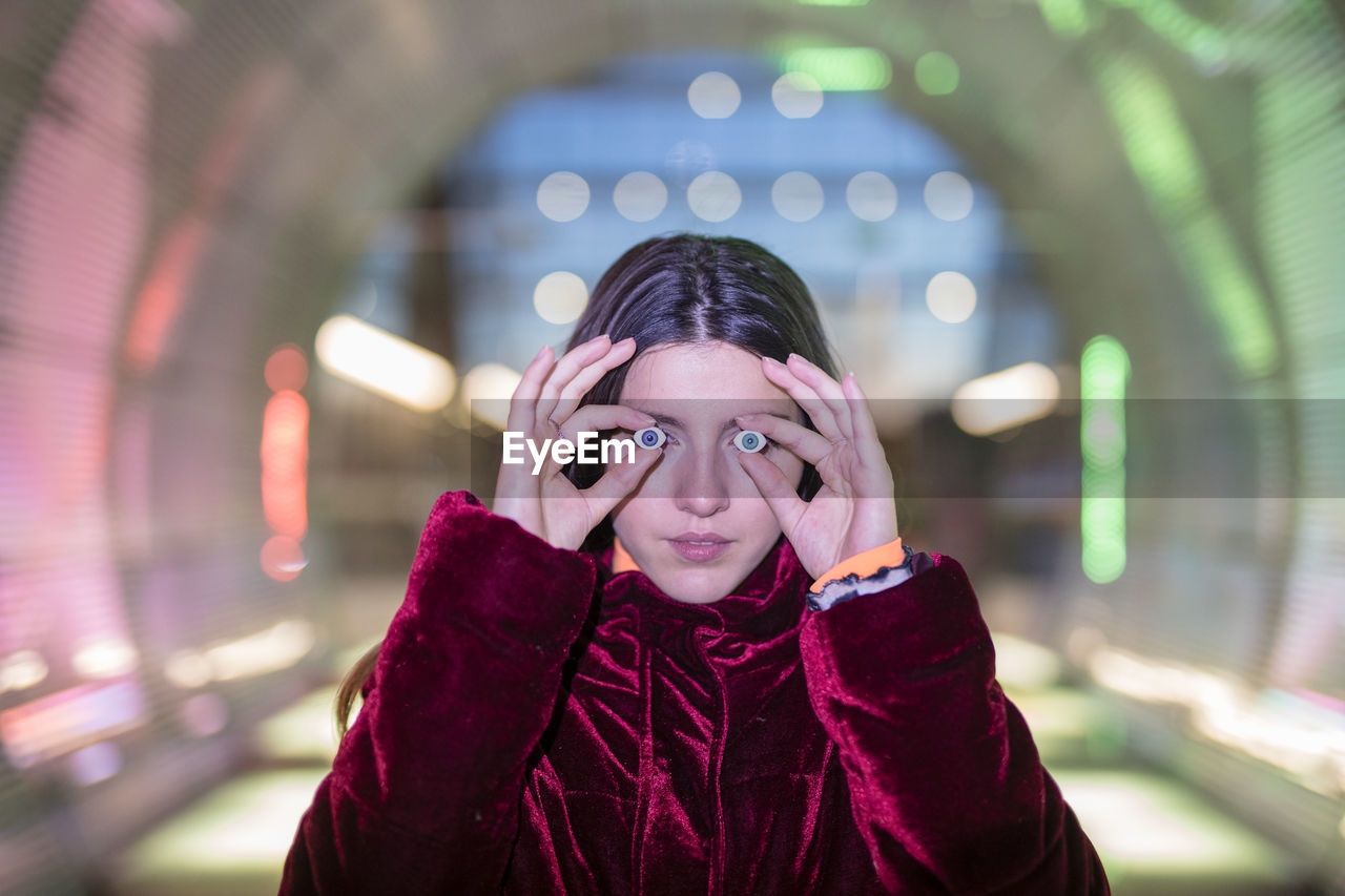 front view, one person, real people, portrait, headshot, lifestyles, illuminated, leisure activity, looking at camera, clothing, focus on foreground, warm clothing, standing, winter, night, young adult, childhood, young women, scarf, innocence