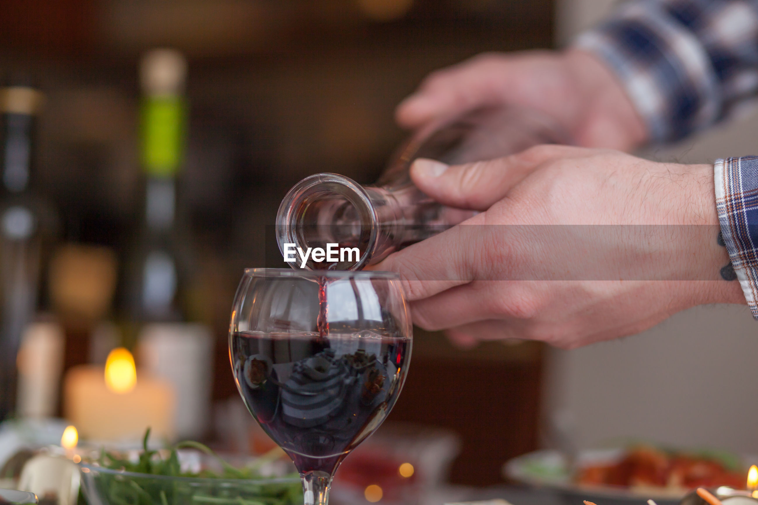 Close up of unrecognizable person pouring wine from a decanter.