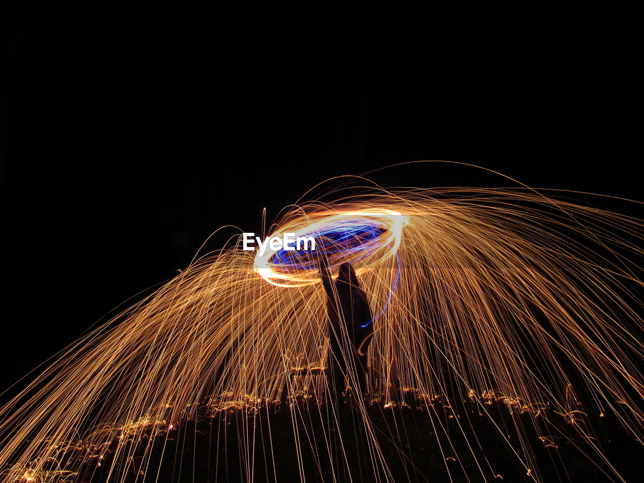 Man standing amidst wire wool at night