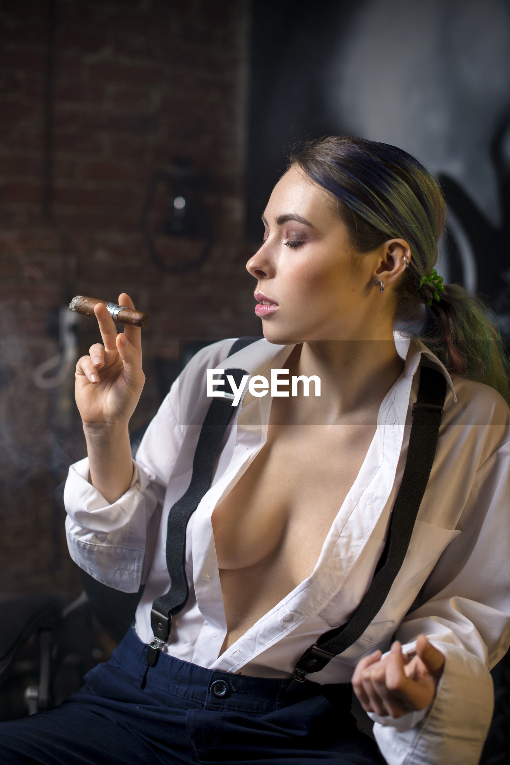 Sensuous woman with eyes closed smoking cigar