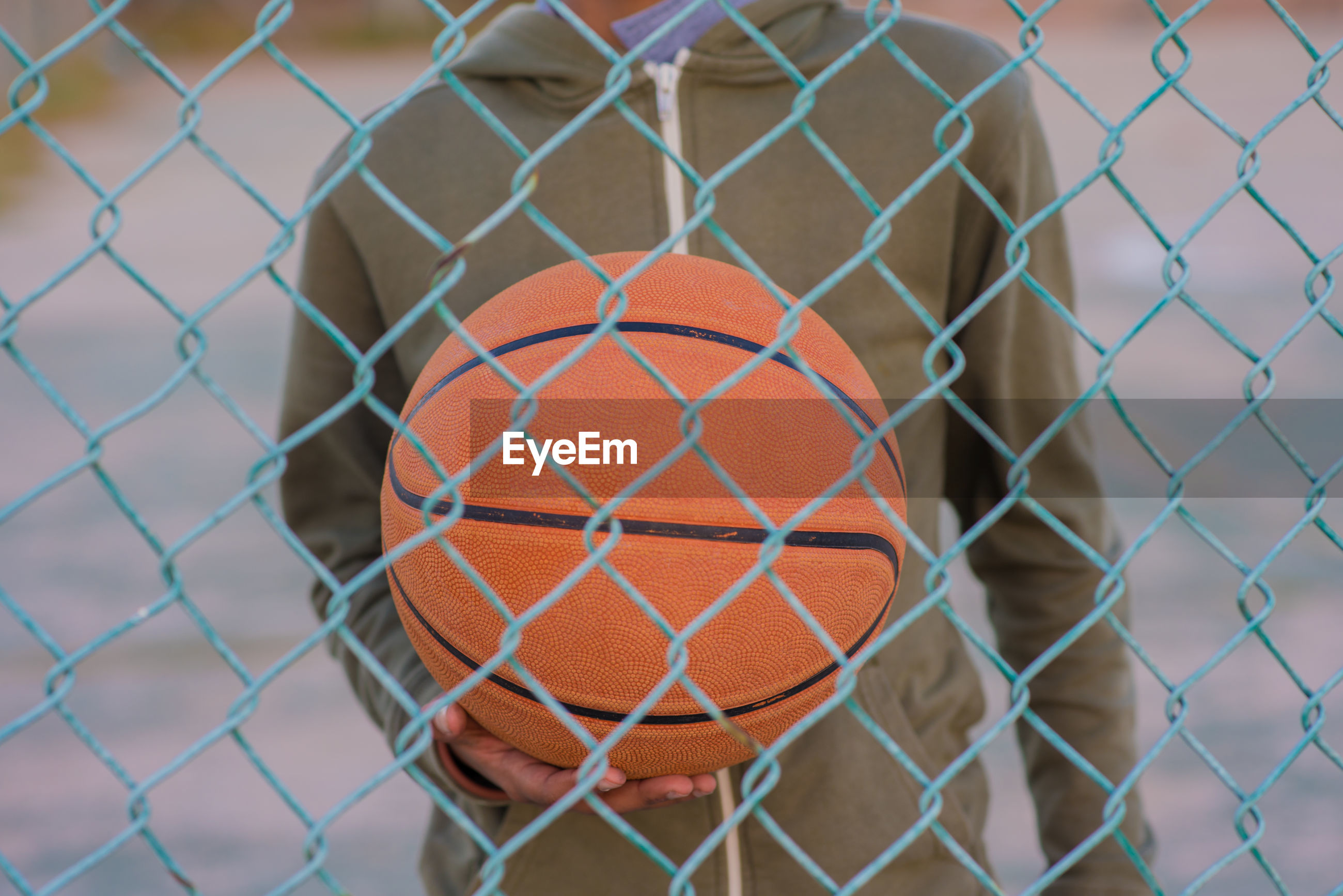 Midsection of boy holding ball while standing on basketball court seen though chainlink fence