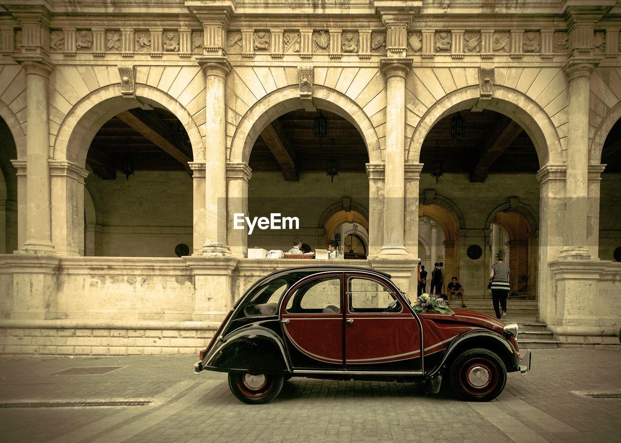 Vintage car against historic building
