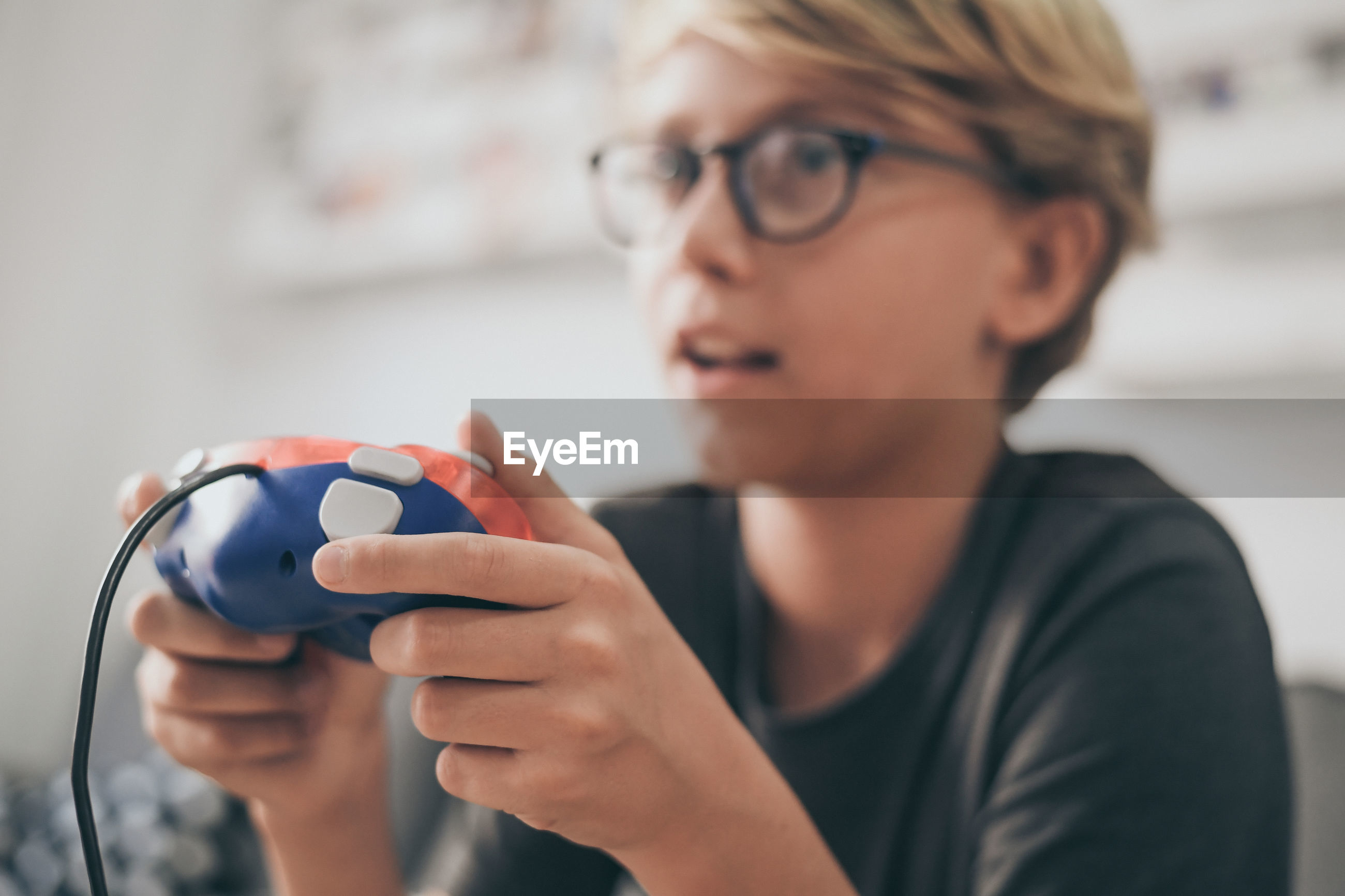 Close-up of cute boy playing video game at home