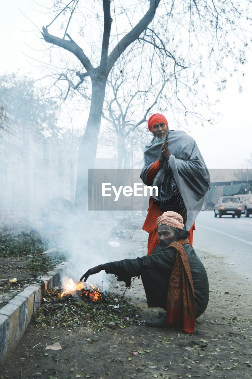Portrait of sadhu by bonfire during winter
