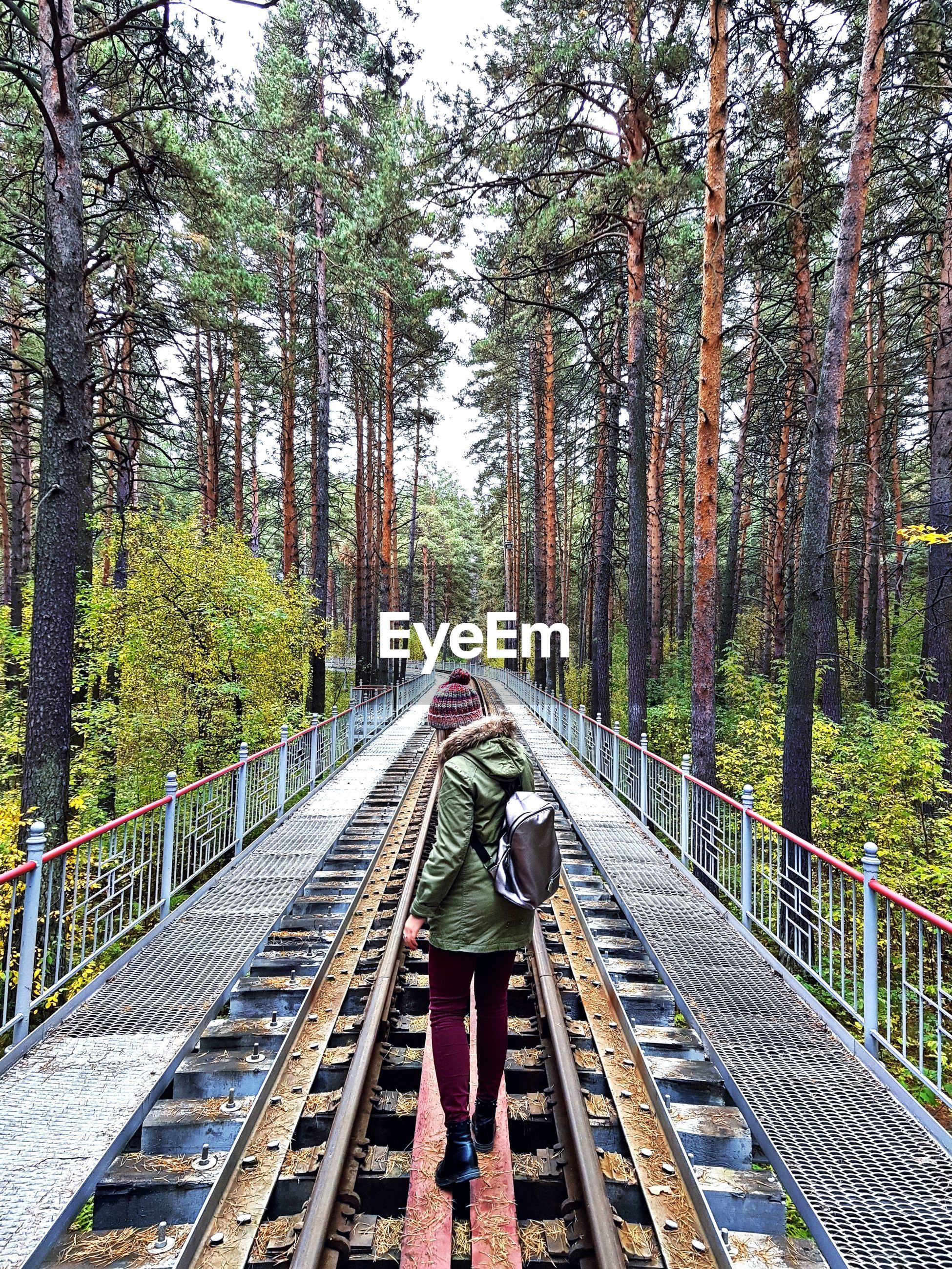 Full length rear view of woman walking on railway bridge amidst trees in forest