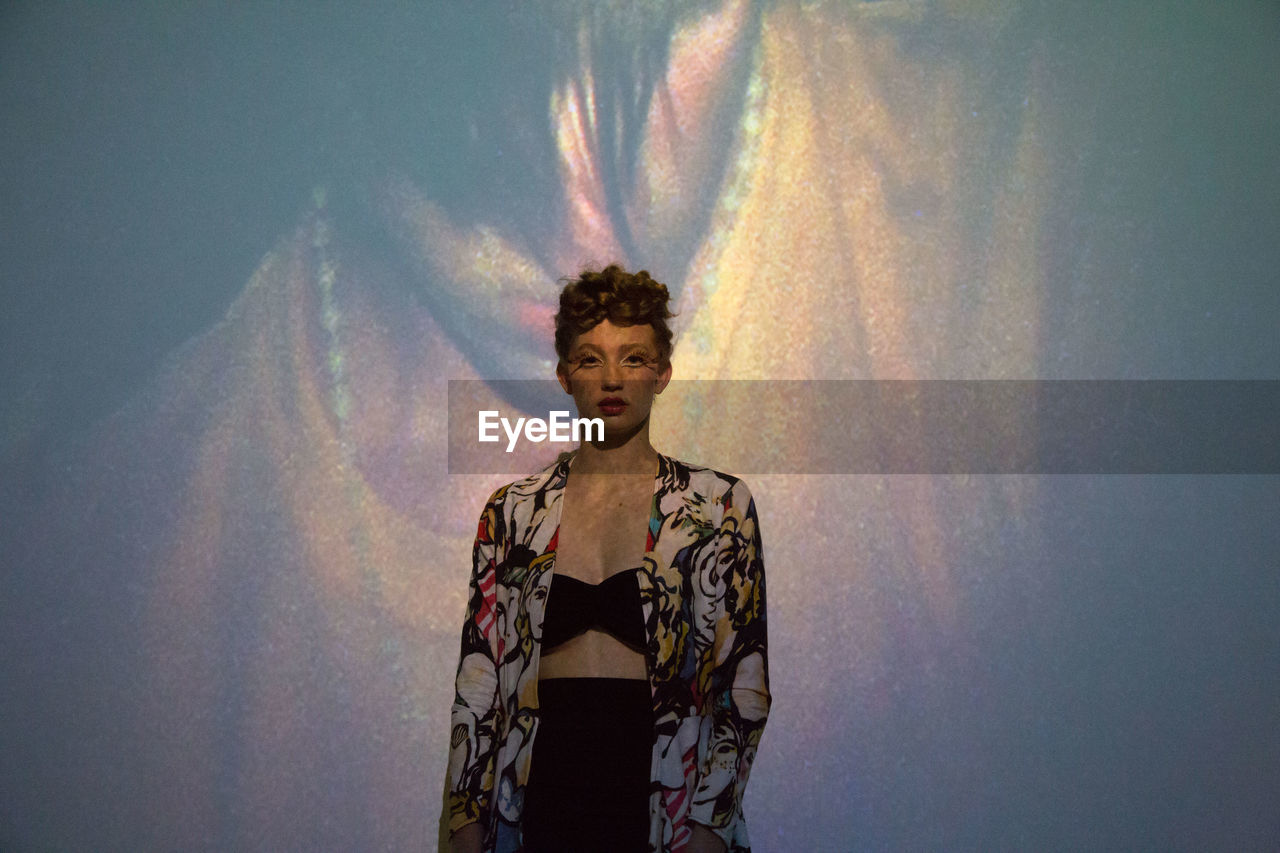 Portrait of fashion model standing against projection screen