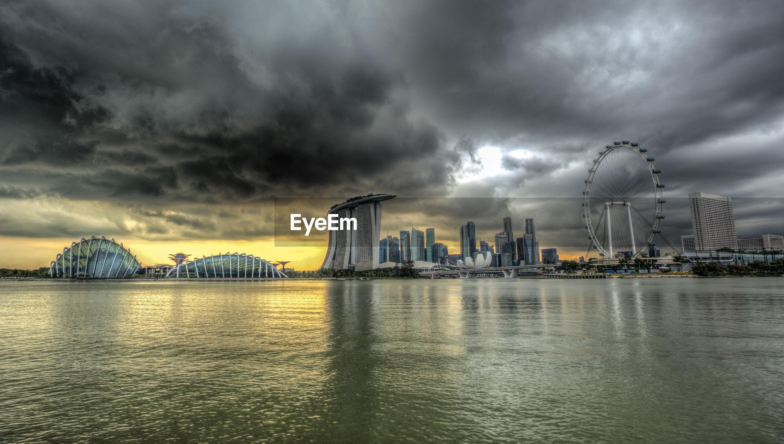 Urban skyline and ferris wheel against sky