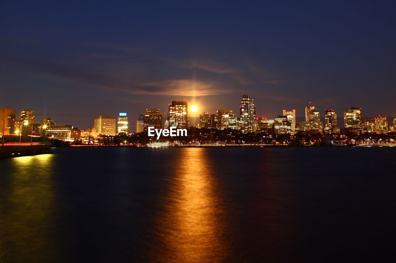 architecture, building exterior, city, built structure, sky, night, illuminated, waterfront, water, cityscape, building, urban skyline, landscape, reflection, no people, cloud - sky, nature, office building exterior, sea, skyscraper, outdoors, nightlife