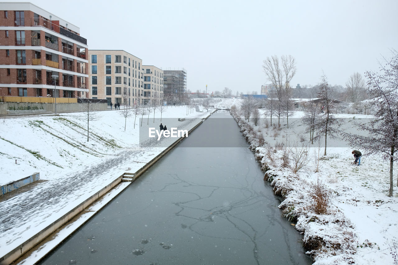 SNOW COVERED ROAD BY CANAL AGAINST SKY