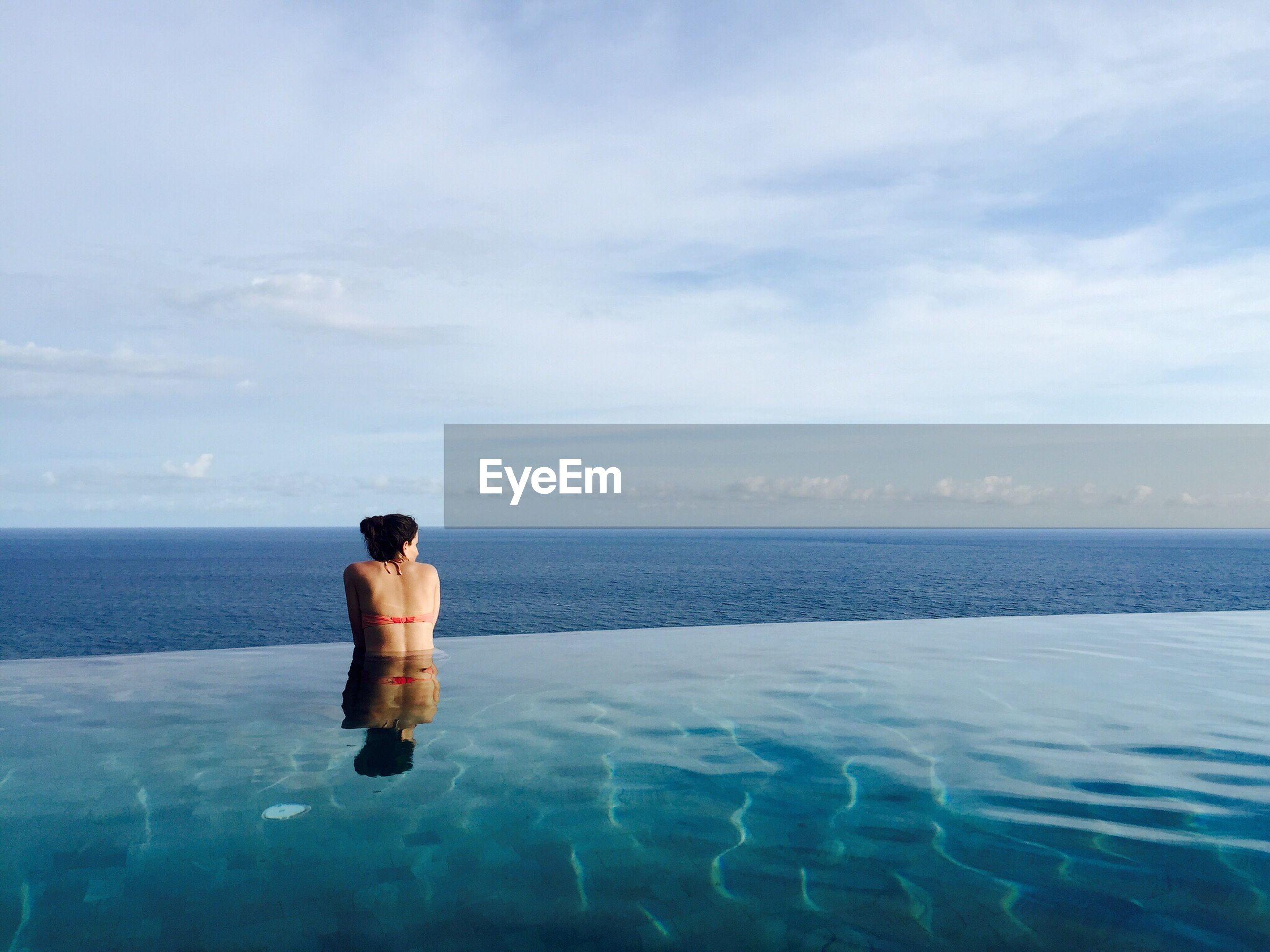 Rear view of woman in infinity pool against sea