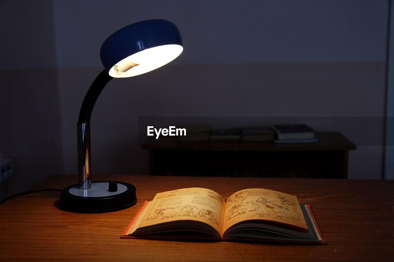 Close-up of electric lamp and book on table