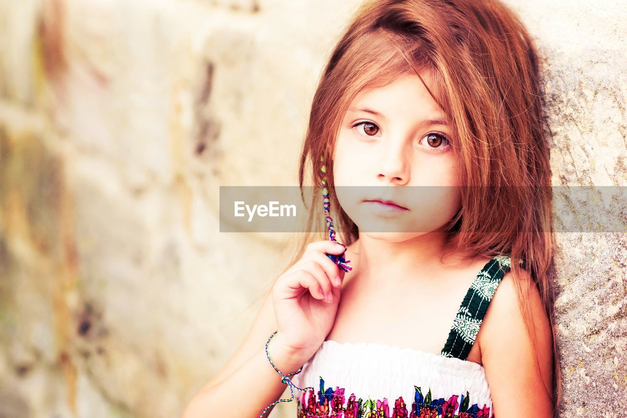 Close-Up Portrait Of Cute Girl Holding Hair Leaning On Wall