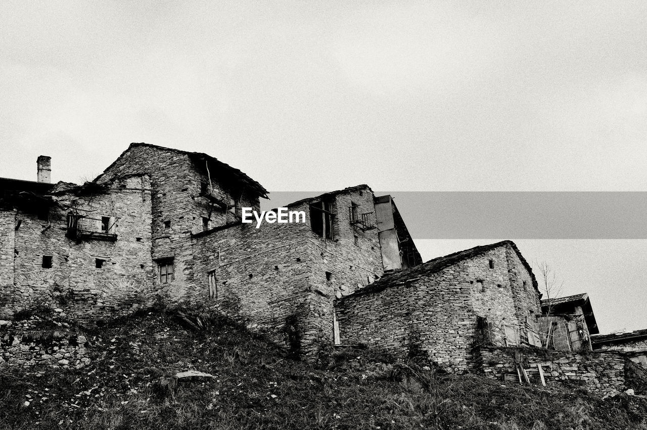 architecture, built structure, building exterior, building, sky, history, house, the past, old, copy space, clear sky, low angle view, nature, no people, abandoned, day, residential district, castle, outdoors, damaged, ruined, stone wall