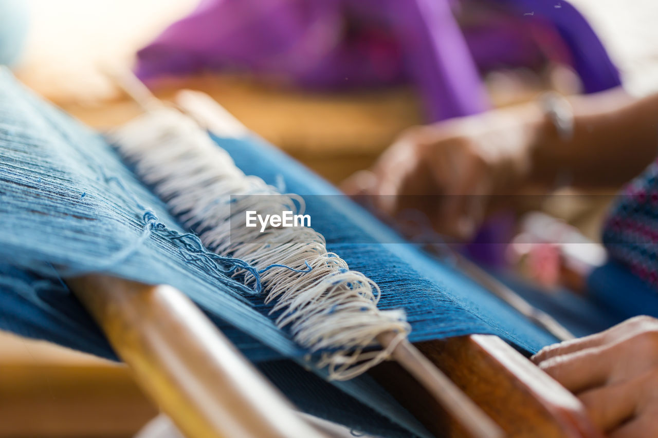 Close-up of woman working on loom