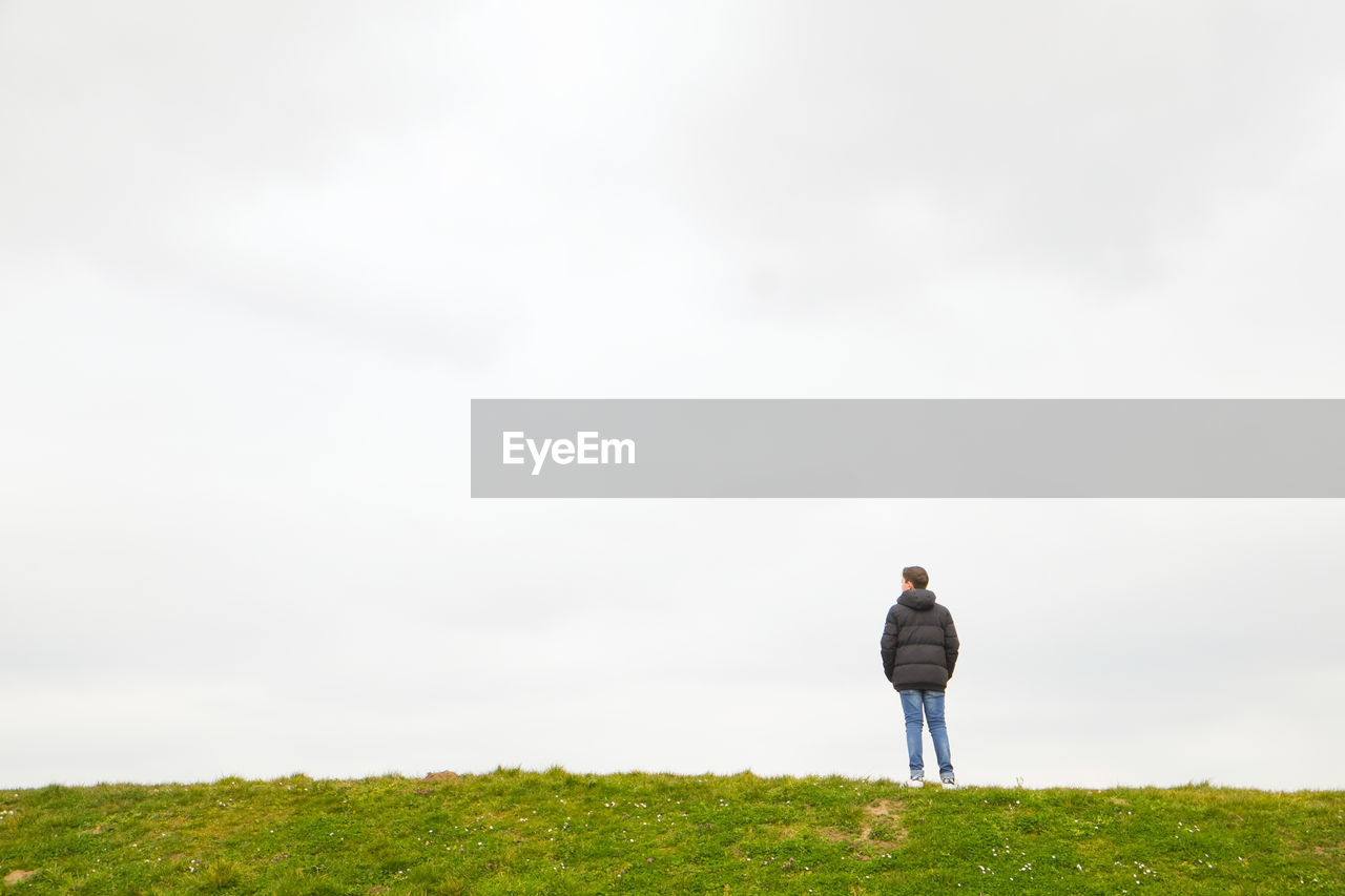 one person, rear view, land, real people, grass, field, sky, leisure activity, day, full length, lifestyles, plant, nature, beauty in nature, men, standing, copy space, casual clothing, green color, outdoors, looking at view
