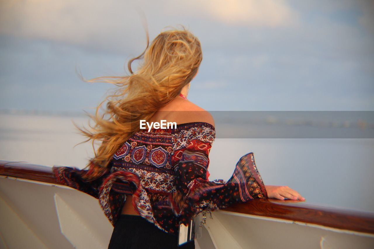 Rear view of woman standing at boat deck against sky