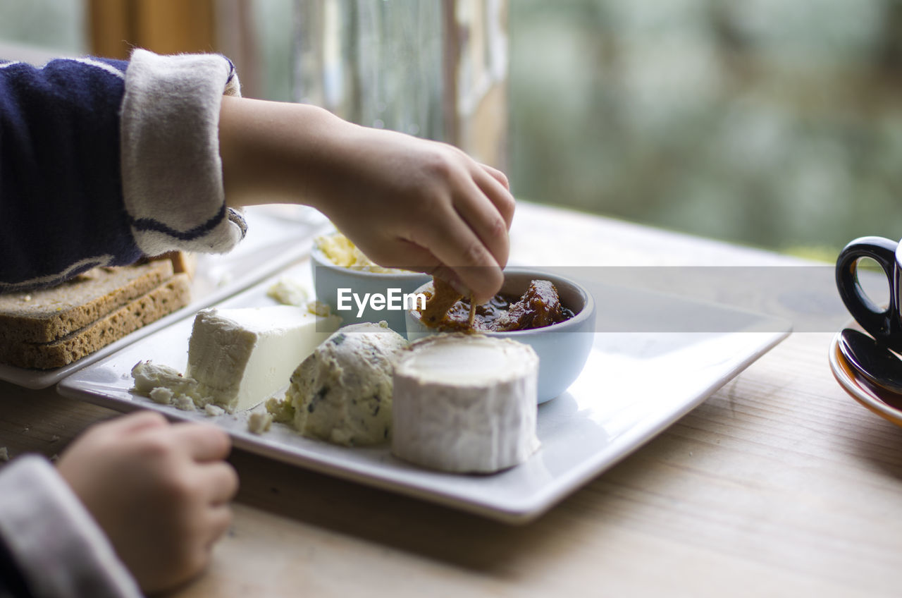 food and drink, one person, food, human hand, table, real people, holding, hand, selective focus, human body part, freshness, unrecognizable person, plate, lifestyles, eating utensil, indoors, ready-to-eat, adult, leisure activity, human limb, breakfast, temptation