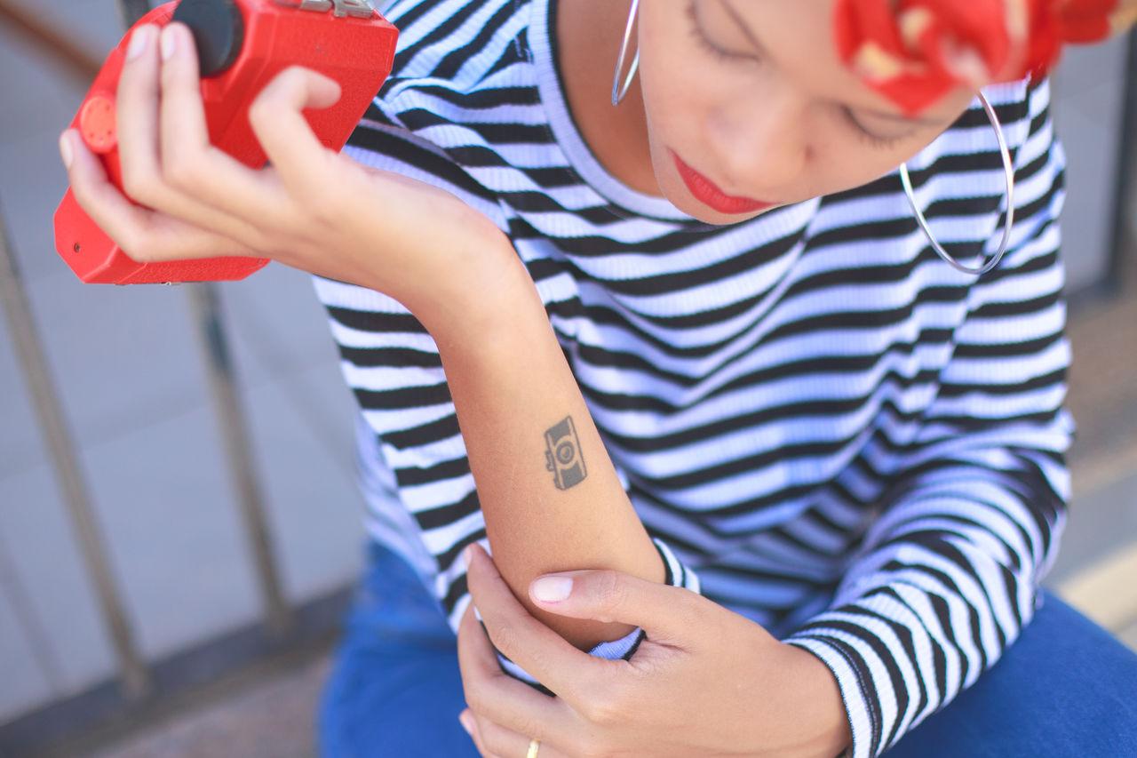Close-Up Of Woman Looking At Tattoo