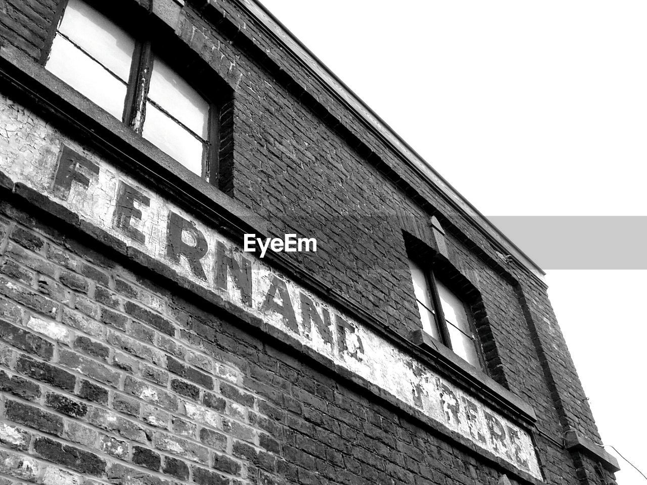 low angle view, building exterior, architecture, built structure, text, window, no people, brick wall, day, outdoors, clear sky, sky