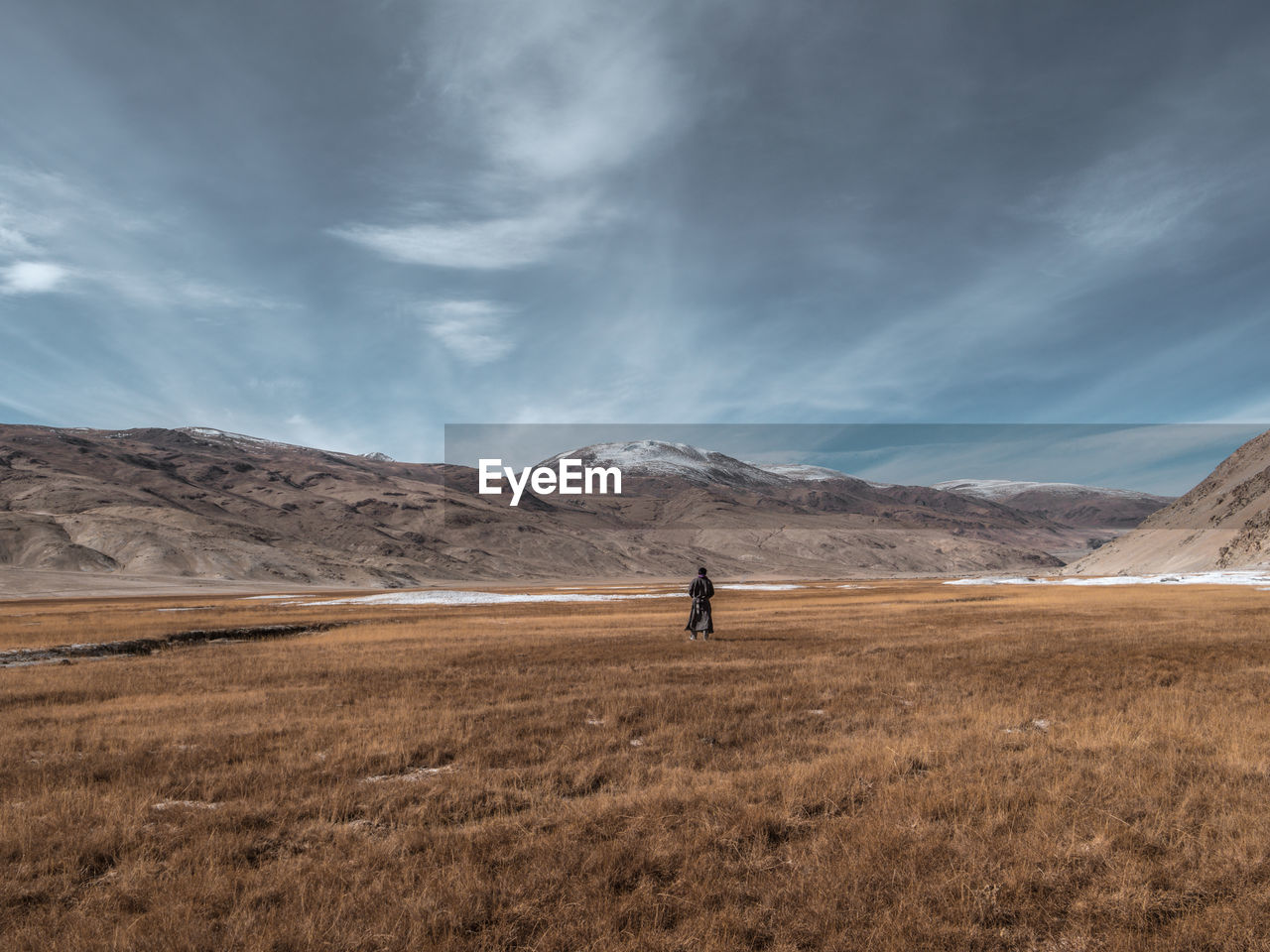 Rear view of young man walking on landscape against sky