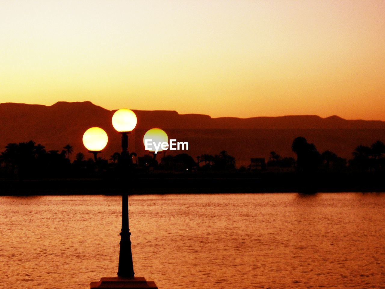 sunset, silhouette, water, scenics, sun, tranquil scene, nature, beauty in nature, orange color, lake, outdoors, reflection, tranquility, clear sky, mountain, sky, tree, no people, illuminated, day