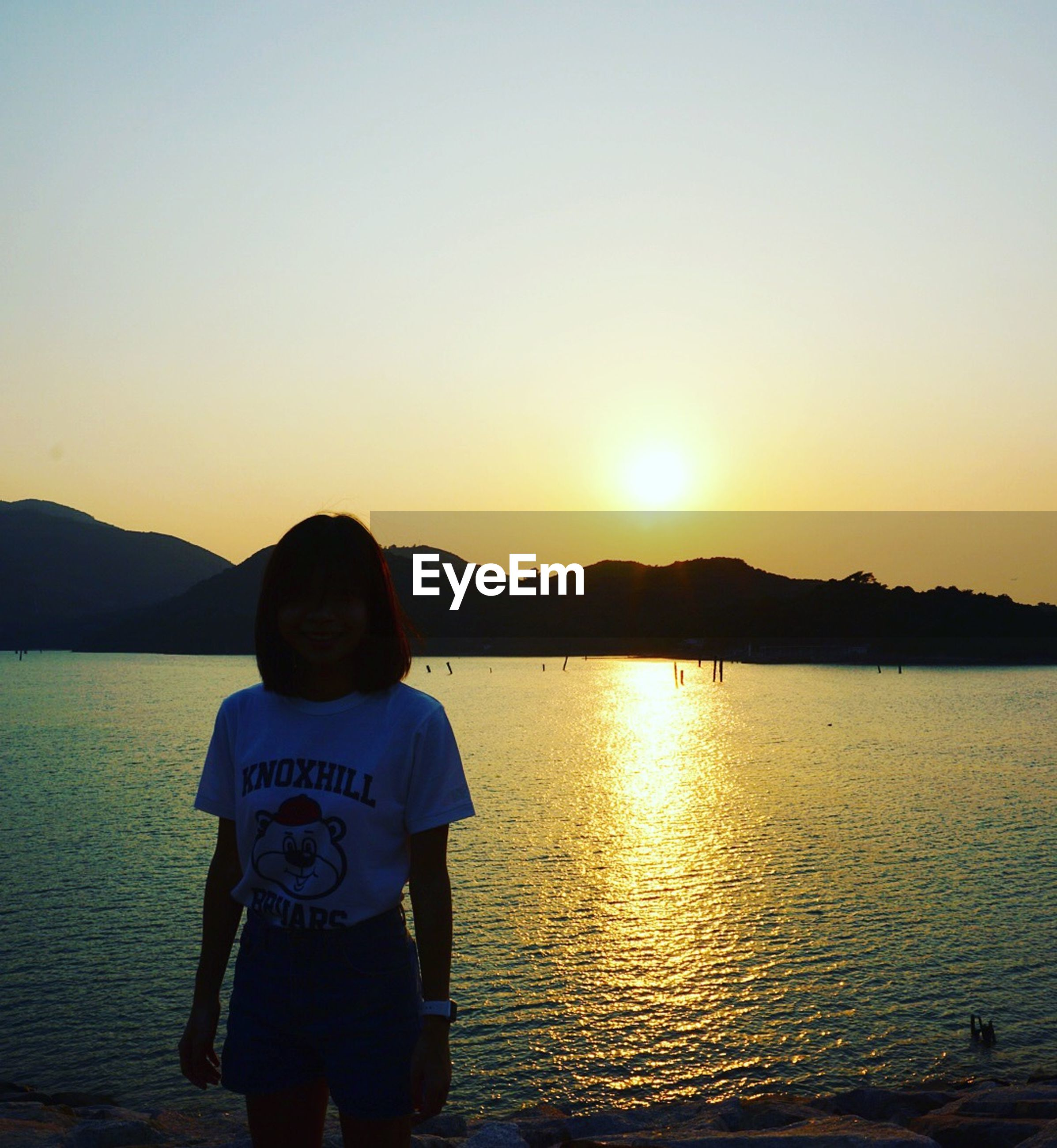 sunset, water, scenics, tranquil scene, tranquility, clear sky, beauty in nature, orange color, sun, standing, copy space, lifestyles, leisure activity, reflection, nature, lake, idyllic, mountain