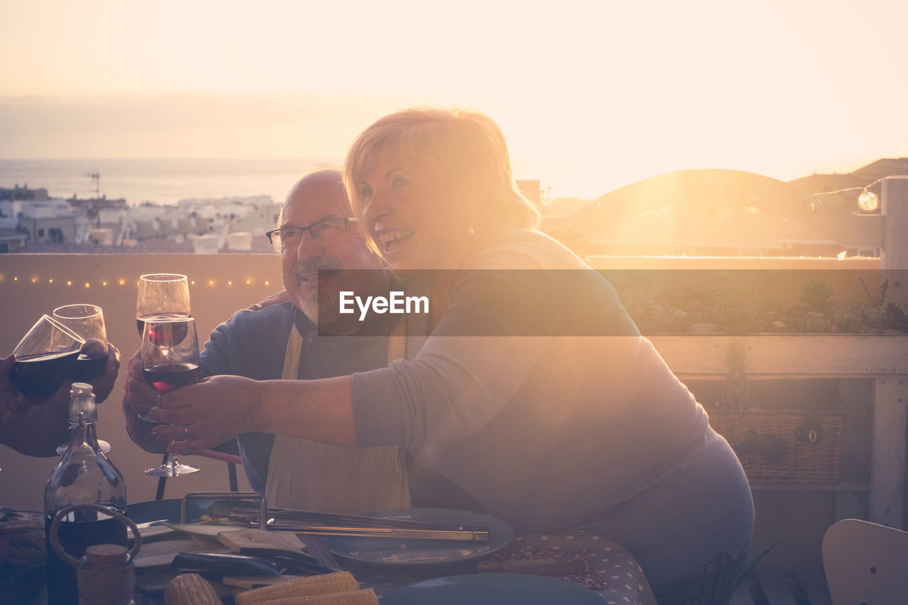 Smiling Senior Couple Toasting Drink At Table In Restaurant During Sunset