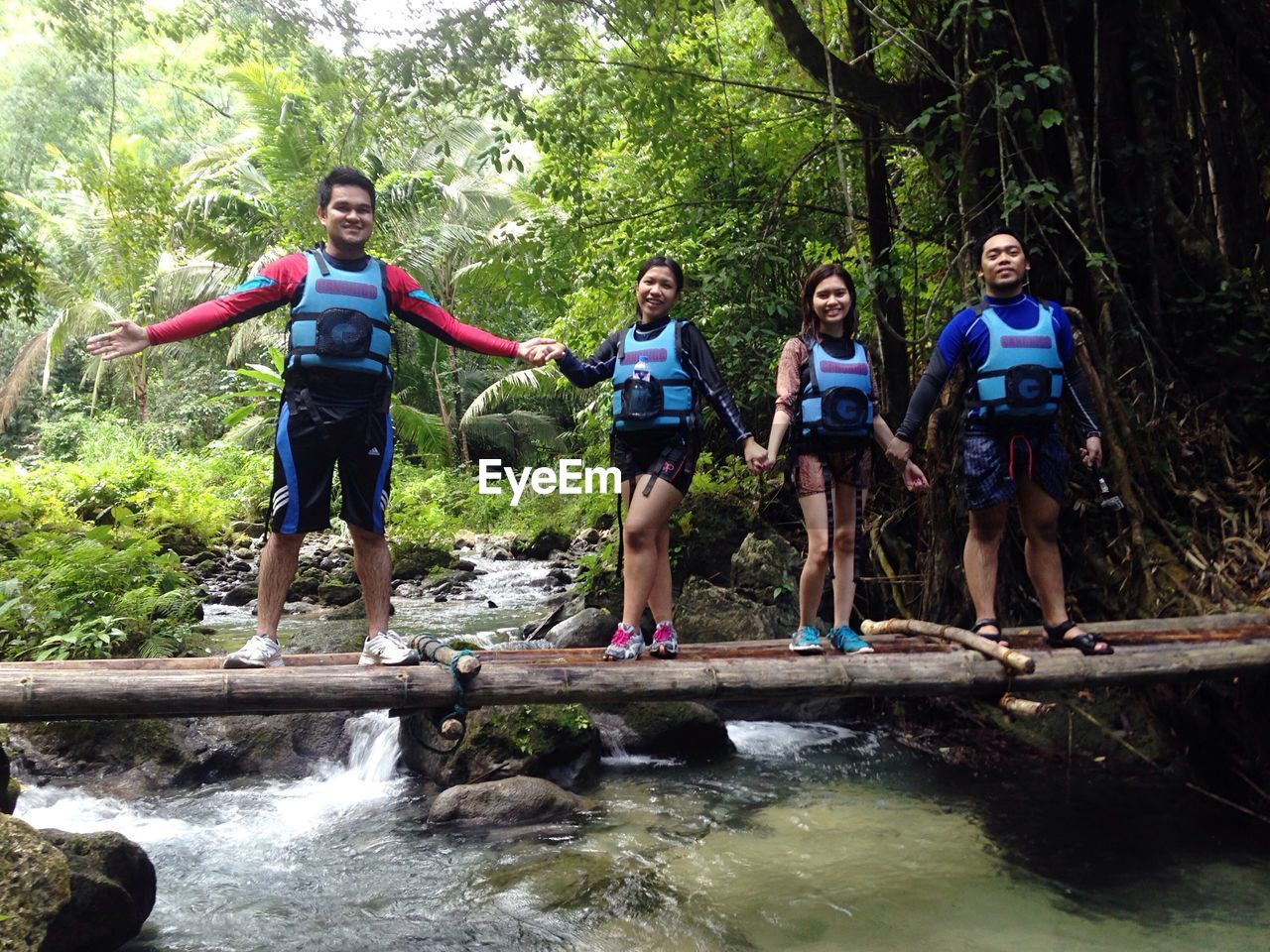 forest, full length, tree, adventure, day, friendship, front view, leisure activity, fun, outdoors, casual clothing, togetherness, enjoyment, water, vitality, young adult, looking at camera, nature, real people, standing, portrait, young women, happiness, vacations, people, healthy lifestyle, smiling, teamwork, adult, adults only